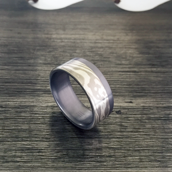 Mokume-gane ring with tantalum liner and single rail. Featuring silver and palladium mokume. Pricing starts at $1990 - contact us for a quote.