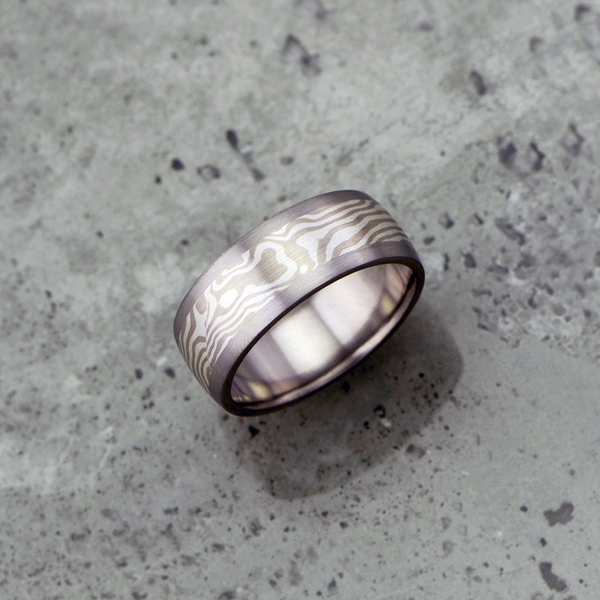 Mokume-gane ring with titanium liner and rails. Featuring white gold and silver mokume. Pricing starts at $1790 - contact us for a quote.