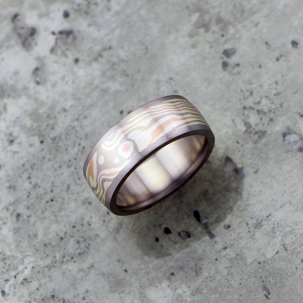 Mokume-gane ring with titanium liner and rails. Featuring rose gold, white gold and silver mokume. Pricing starts at $1790 - contact us for a quote.