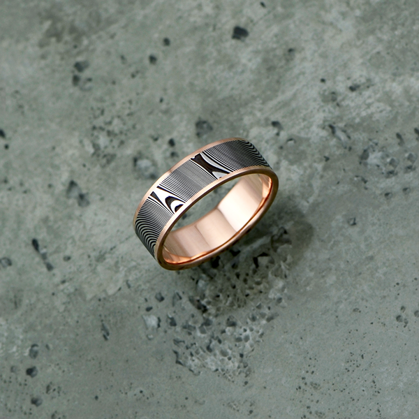 Damascus steel ring with an 18ct rose gold liner and rails, in a dark etch and flat profile. Price depends on size - see pricing tab below.