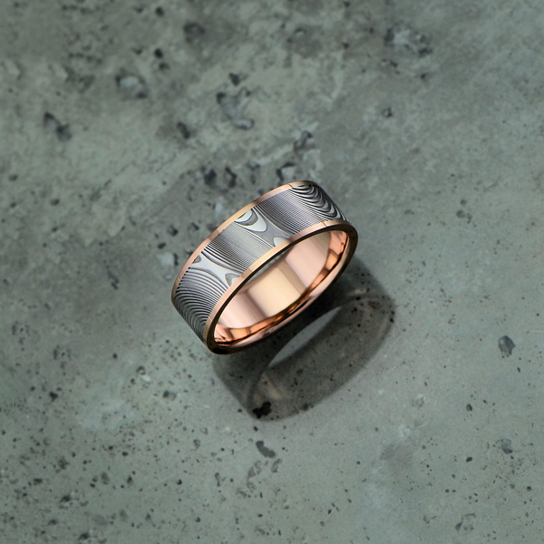 Damascus steel ring with an 18ct rose gold liner and rails, in a light etch and flat profile. Price depends on size - see pricing tab below.