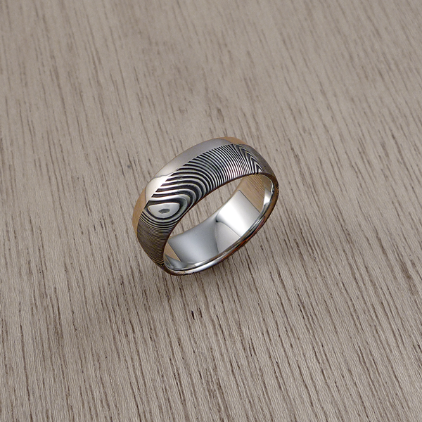 Damascus steel ring with a single 18ct white gold rail, in a dark etch and round profile. $1550 + shipping.