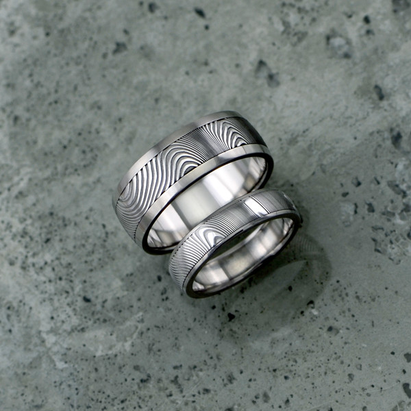 Damascus + liner & rails design in titanium. Featuring a light etch and round profile. $1500 each + shipping - all sizes.