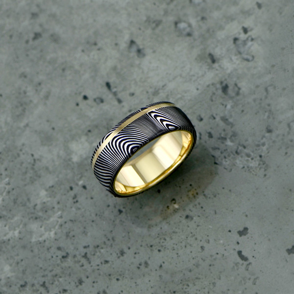 Damascus steel ring with an 18ct yellow gold liner and inlay, in a dark etch and round profile. Price depends on size - see pricing tab below.