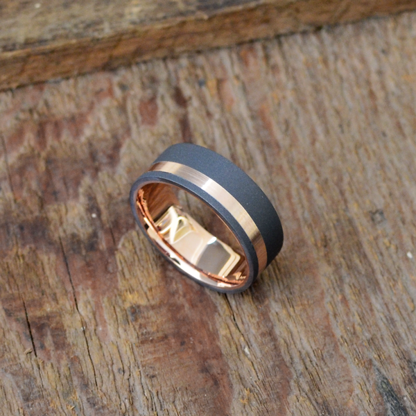 Sandblasted tantalum + 18ct gold liner & inlay. Comes in yellow, white or rose gold. Prices starts at $2040 for sizes up to & inc. T at 7-8mm wide.