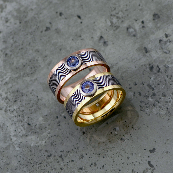 Damascus steel ring with an 18ct gold liner and rails. Bezel set light purple sapphire. Flat profile only. *Priced from $3500 each + shipping.