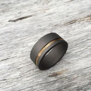 Sandblasted titanium ring with a 9ct gold wire inlay.