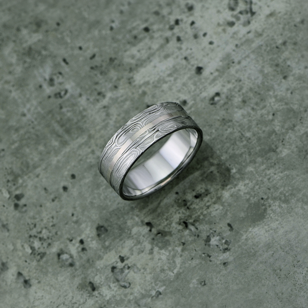 Custom patterned Damascus steel ring with 18ct white gold centre inlay, in a light etch and flat profile. $1350 + shipping.