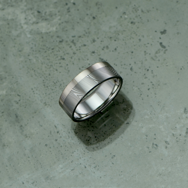 Damascus steel ring with single 18ct white gold rail. Flat profile. Light etch.