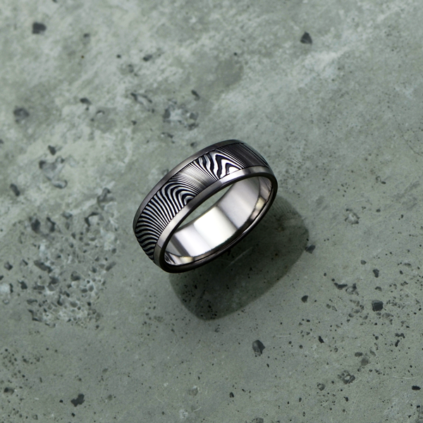 Damascus steel ring with a titanium liner and rails, in a dark etch and round profile. $1500 + shipping - all sizes.