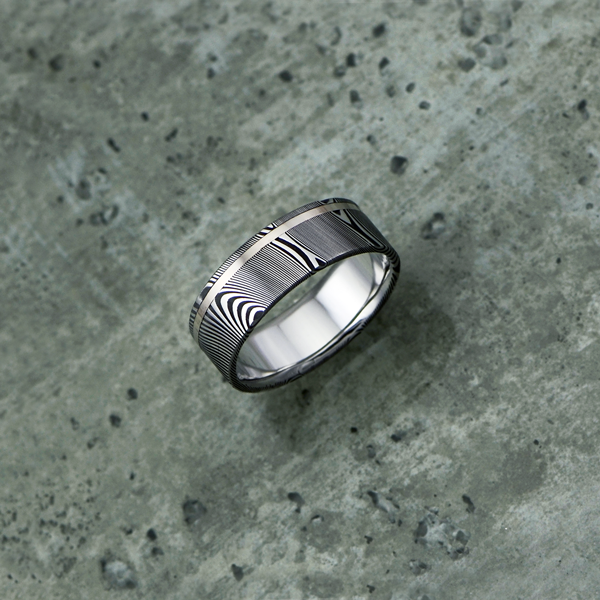 Damascus steel ring with an 18ct white gold off-centre inlay, in a dark etch and flat profile. $1350 + shipping.