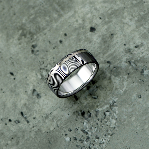 Damascus steel ring with an 18ct white gold off-centre inlay, in a dark etch and round profile. $1350 + shipping.