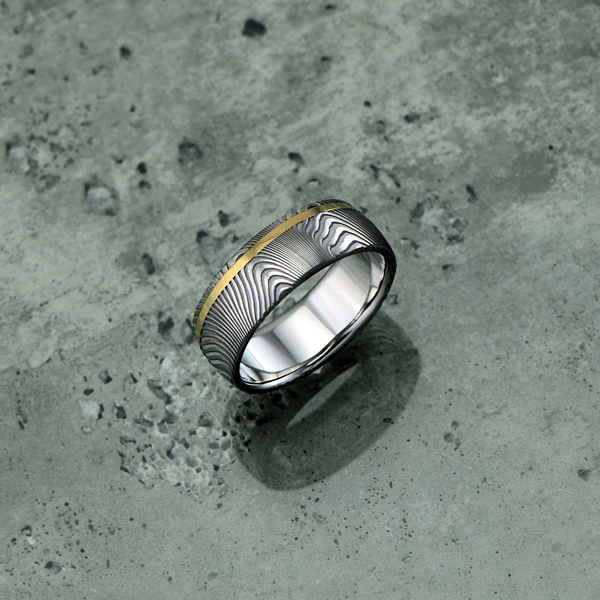 Damascus steel ring with an 18ct yellow gold off-centre inlay, in a light etch and round profile. $1350 + shipping.