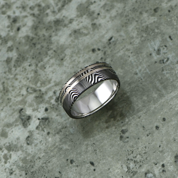 Damascus steel ring with 18ct white gold inlays, in a dark etch and round profile. $1550 + shipping.