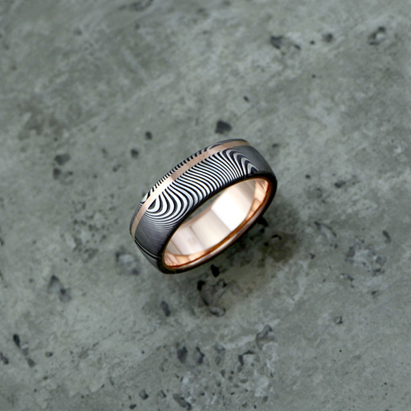 Damascus steel ring with an 18ct rose gold liner and inlay, in a dark etch and round profile. Price depends on size - see pricing tab below.