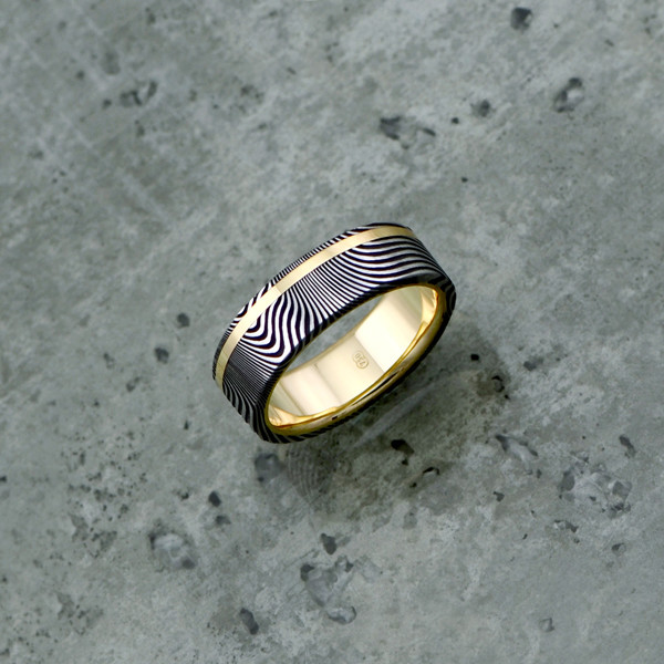 Damascus steel ring with an 18ct yellow gold liner and inlay, in a dark etch and flat profile. Price depends on size - see pricing tab below.