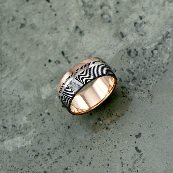 Custom Damascus steel ring with an 18ct rose gold liner and single rail + 18ct white gold inlay. Prices start at $2190 for up to and inc. size T .