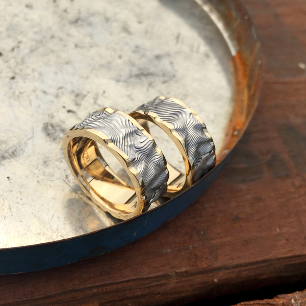 Custom rough finish Damascus steel ring with an 18ct yellow gold liner and rails (light etch only). Prices start at $1990 for up to and inc. size T .