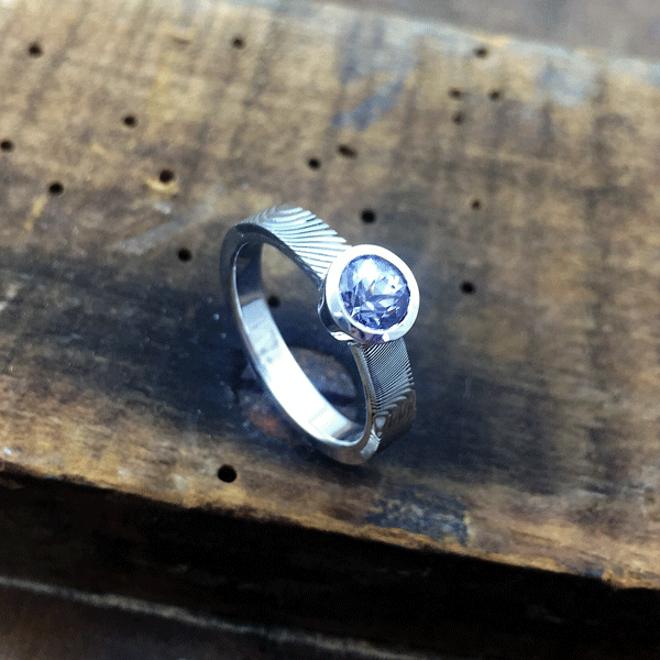 Solitaire engagement ring. Damascus steel shoulders with white gold band. Bezel set light purple sapphire. *Priced from $3000 + shipping.